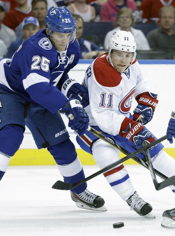 Montreal Canadiens right wing Brendan Gallagher (11) moves the puck around Tampa Bay Lightning defenseman Matt Carle (25) during the first period of Game 1 of a first-round NHL hockey playoff series on Wednesday, April 16, 2014, in Tampa, Fla
