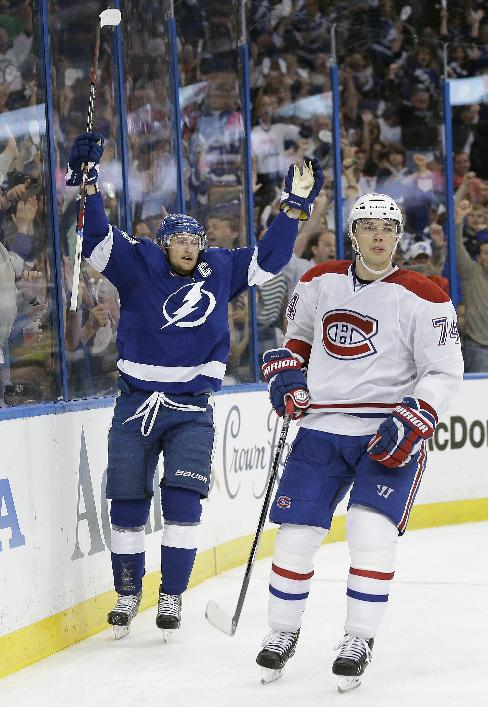 Tampa Bay Lightning center Steven Stamkos (91) celebrates behind Montreal Canadiens defenseman Alexei Emelin (74), of Russia, after scoring during the second period of Game 1 of a first-round NHL hockey playoff series on Wednesday, April 16, 2014, in Tampa, Fla