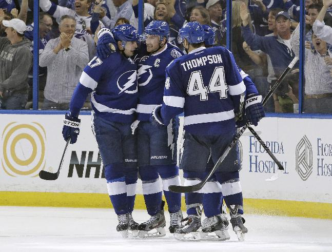 Tampa Bay Lightning center Steven Stamkos (91) celebrates with teammates Alex Killorn (17) and Nate Thompson (44) after scoring against the Montreal Canadiens during the third period of Game 1 of a first-round NHL hockey playoff series on Wednesday, April 16, 2014, in Tampa, Fla