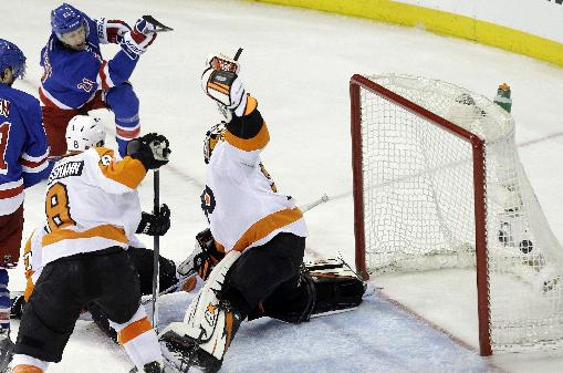 New York Rangers' Derek Stepan (21) shoots the puck past Philadelphia Flyers goalie Ray Emery (29) during the third period in Game 1 of an NHL hockey first-round playoff series on Thursday, April 17, 2014, in New York. The Rangers won the game 4-1