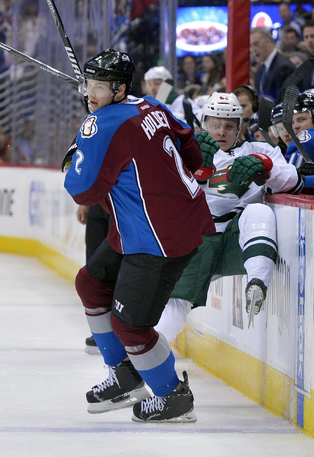Minnesota Wild center Mikael Granlund (64), from Finland, is checked into the boards by Colorado Avalanche defenseman Nick Holden (2) during the first period in Game 1 of an NHL hockey first-round playoff series on Thursday, April 17, 2014, in Denver