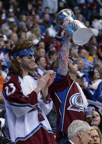 Colorado Avalanche fans hold a foil Stanley Cup before the start of Game 1 of an NHL hockey first-round playoff series against the Minnesota Wild, Thursday, April 17, 2014, in Denver