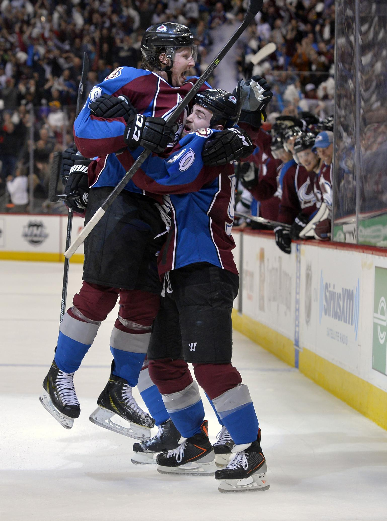 Colorado Avalanche center Ryan O'Reilly (90) is congratulated by teammate Nathan MacKinnon (29) after scoring a goal against the Minnesota Wild during the second period in Game 1 of an NHL hockey first-round playoff series on Thursday, April 17, 2014, in Denver