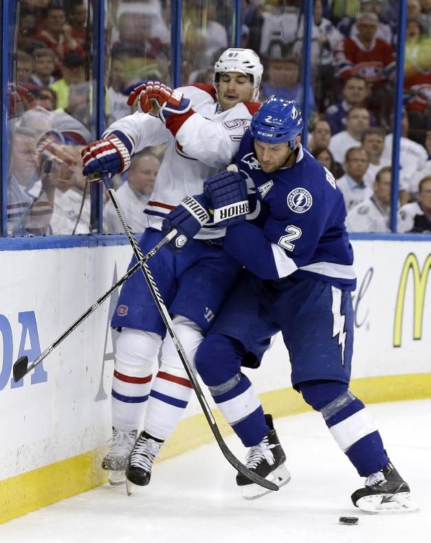 Tampa Bay Lightning defenseman Eric Brewer (2) checks Montreal Canadiens left wing Max Pacioretty (67) into the boards during the first period of Game 2 of a first-round NHL hockey playoff series on Friday, April 18, 2014, in Tampa, Fla