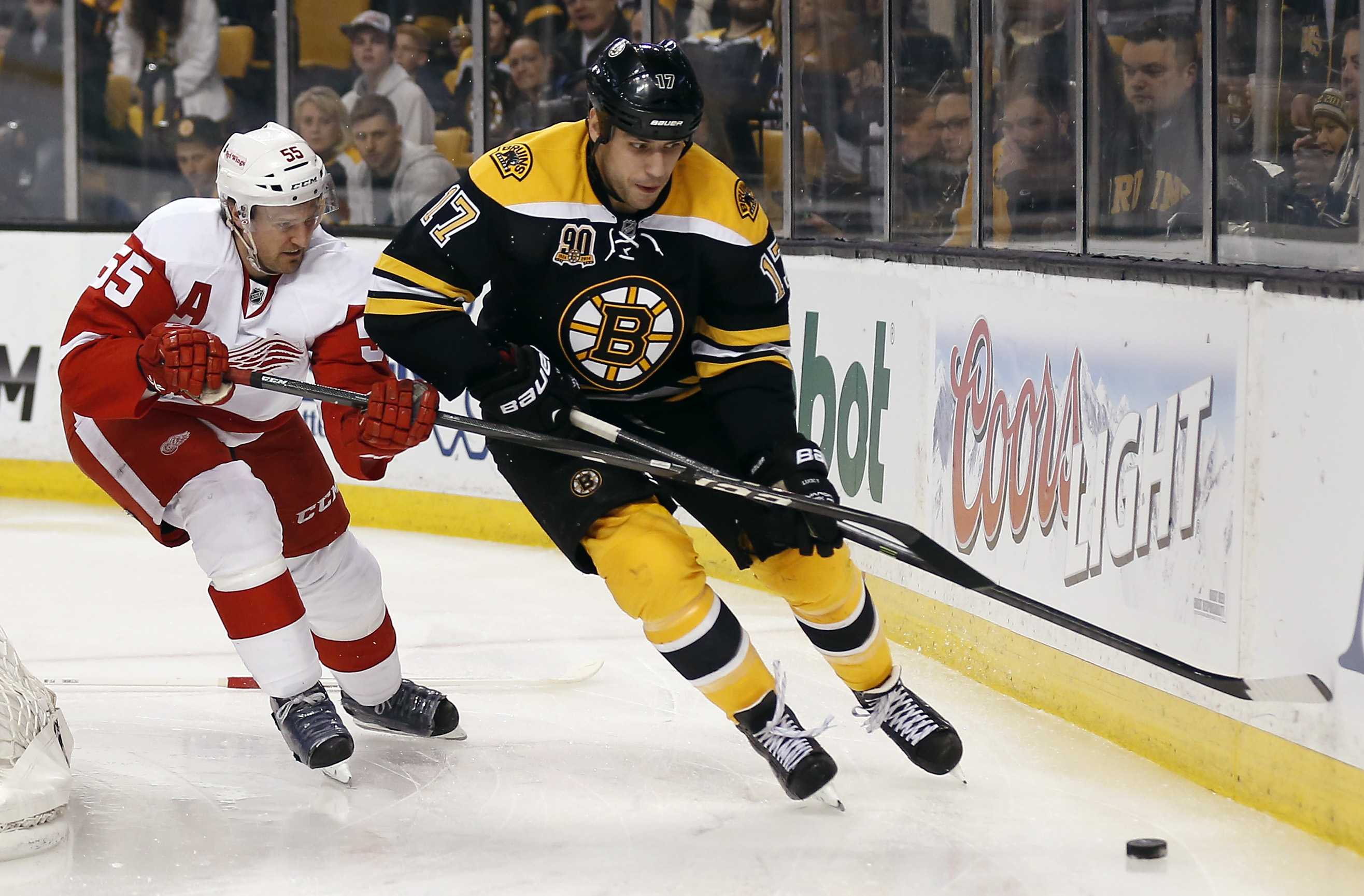 Boston Bruins' Milan Lucic (17) keeps the puck from Detroit Red Wings' Niklas Kronwall during the second period of Game 1 of a first-round NHL playoff hockey series in Boston on Friday, April 18, 2014