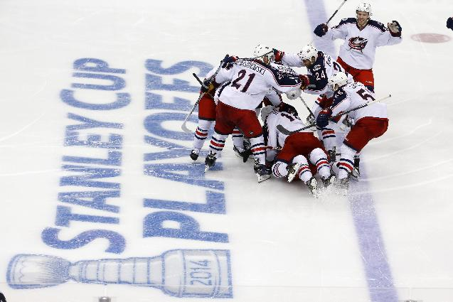 Columbus Blue Jackets' Matt Calvert (11) is buried by teammates after scoring his game-winning goal in the second overtime period of a first-round NHL playoff hockey game against the Pittsburgh Penguins in Pittsburgh, Saturday, April 19, 2014. The Blue Jackets won 4-3, to even the series at 1-1