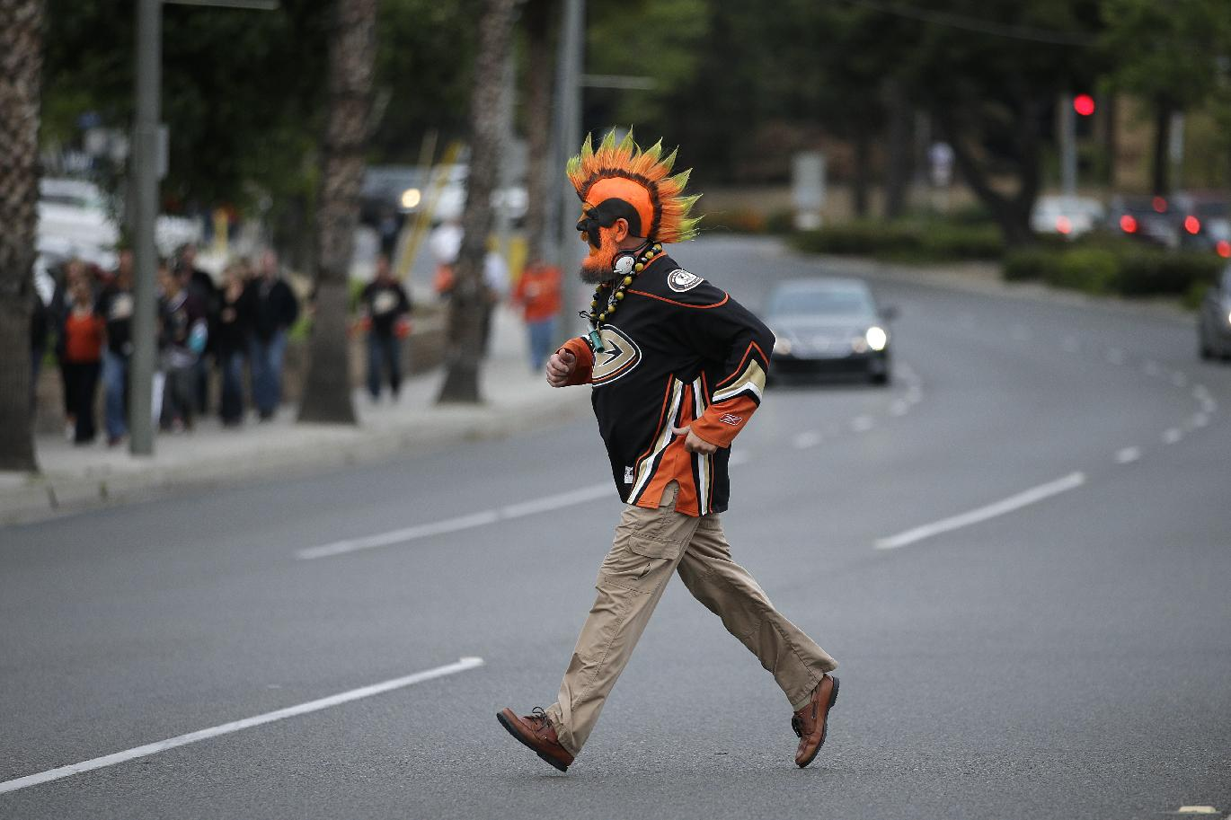 Anaheim Ducks fan Steve Markusic walks across the street on his way to Honda Center  to watch Game 5 of the first-round NHL hockey Stanley Cup playoff series between the Anaheim Ducks and the Dallas Stars on Friday, April 25, 2014, in Anaheim, Calif