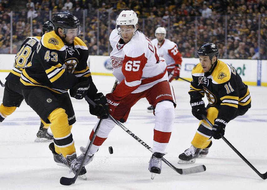 Boston Bruins' Matt Bartkowski (43) and Detroit Red Wings' Danny DeKeyser (65) battle for the puck during the first period in Game 5 in the first round of the NHL hockey Stanley Cup playoffs  in Boston, Saturday, April 26, 2014