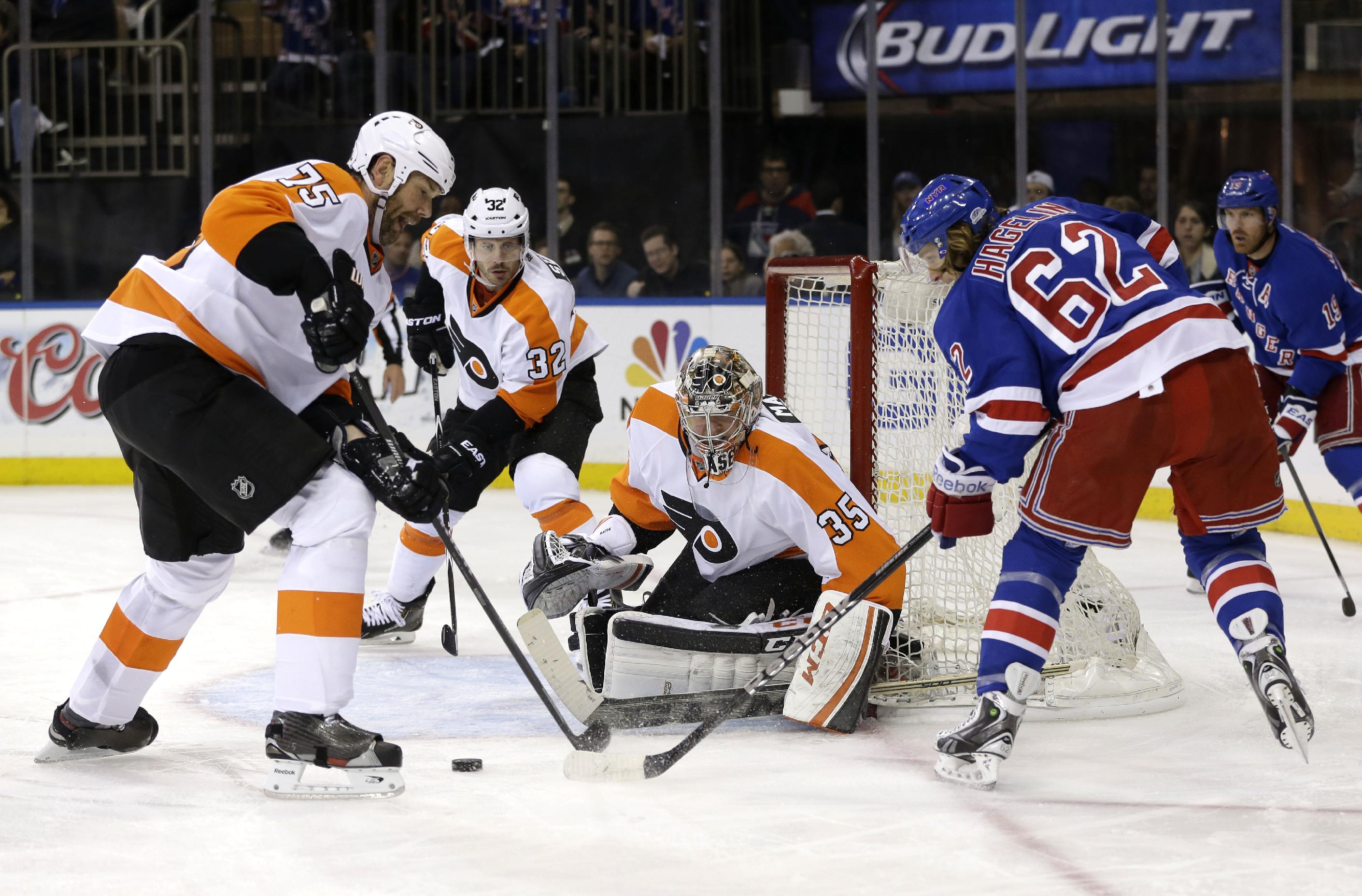 Philadelphia Flyers goalie Steve Mason, center, blocks a shot by New York Rangers' Carl Hagelin, right, as Flyers' Hal Gill, left, and Mark Streit look on during the second period of Game 5 of an NHL hockey first-round playoff series on Sunday, April 27, 2014, in New York