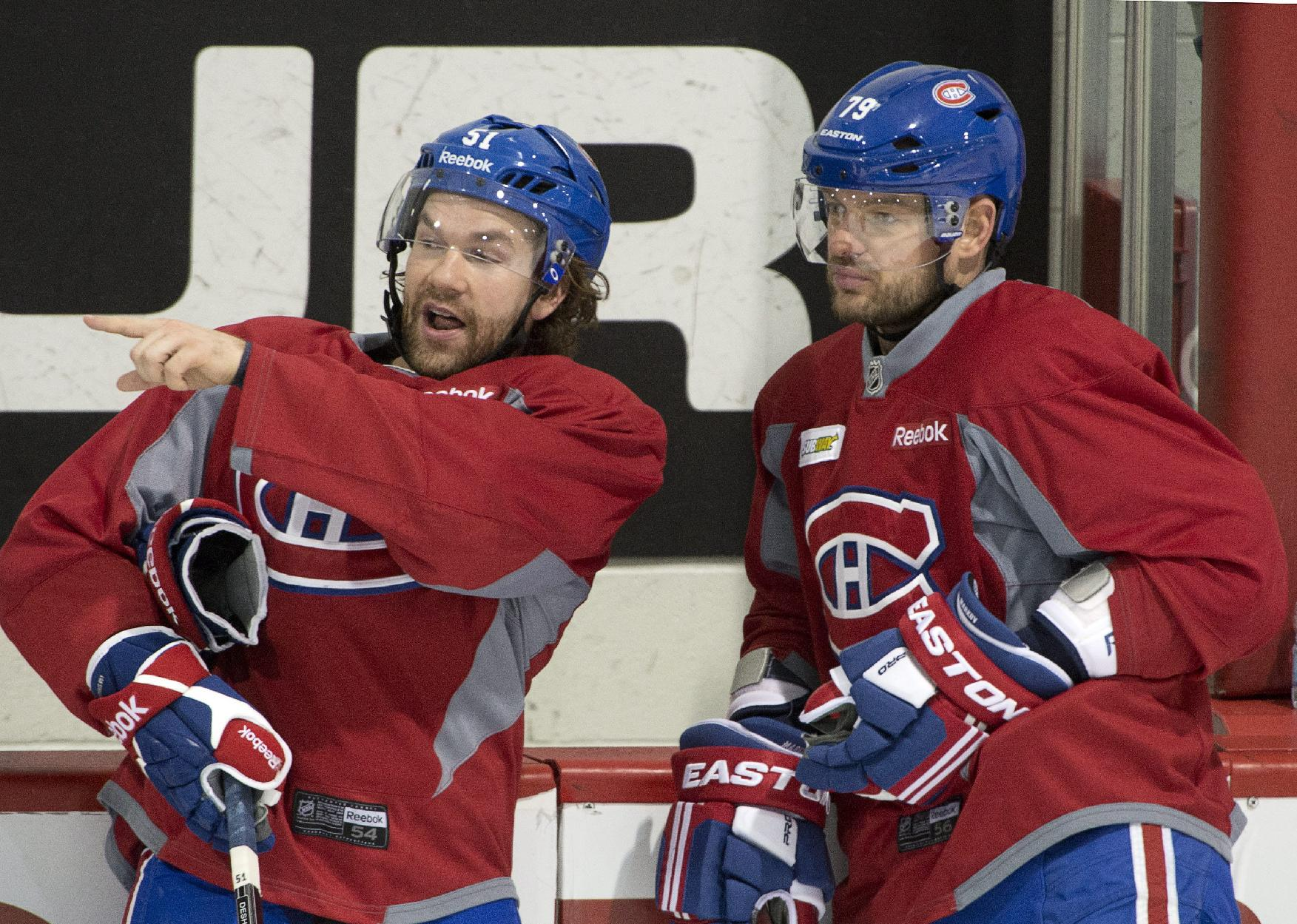 Montreal Canadiens center David Desharnais, left, and defenseman Andrei Markov go over a play during the team's NHL hockey practice Monday, April 28, 2014, in Brossard, Quebec