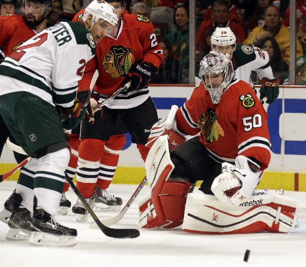Chicago Blackhawks goalie Corey Crawford (50), right, blocks a shot by Minnesota Wild's Nino Niederreiter (22) during the first period  in Game 2 of an NHL hockey second-round playoff series in Chicago, Sunday, May 4, 2014
