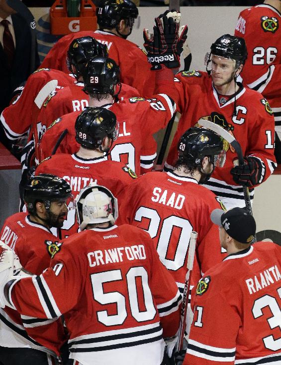 Chicago Blackhawks' Jonathan Toews (19), top right, celebrates with teammates after the Blackhawks defeated the Minnesota Wild 4-1 in Game 2 of an NHL hockey second-round playoff series in Chicago, Sunday, May 4, 2014