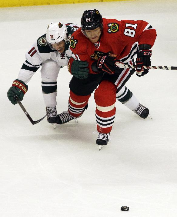 Chicago Blackhawks' Marian Hossa, right, and Minnesota Wild's Zach Parise (11) battle as they chase the puck  during the third period in Game 2 of an NHL hockey second-round playoff series in Chicago, Sunday, May 4, 2014. The Blackhawks won 4-1