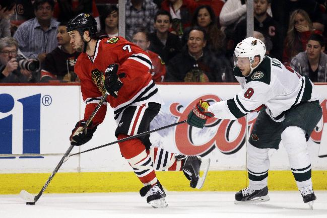 Chicago Blackhawks' Brent Seabrook, left, controls the puck past Minnesota Wild's Cody McCormick during the second period in Game 2 of an NHL hockey second-round playoff series in Chicago, Sunday, May 4, 2014. The Blackhawks won 4-1
