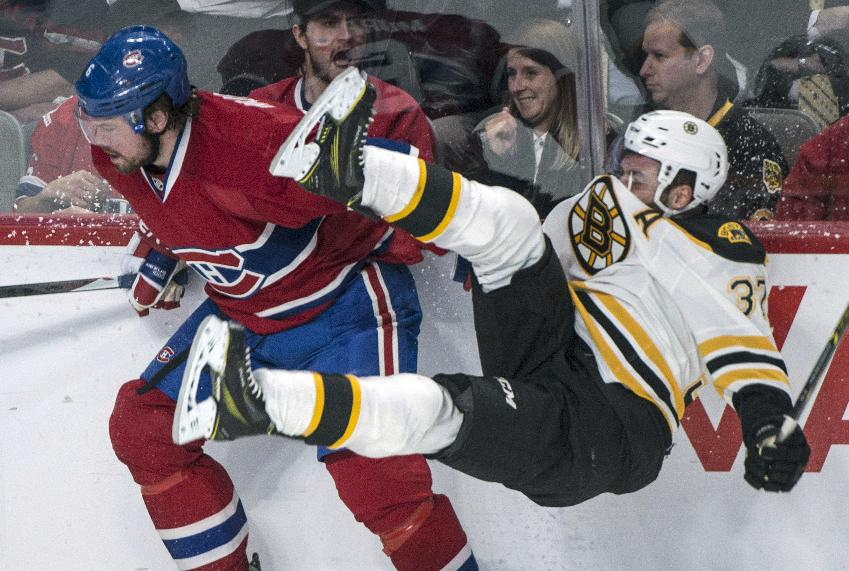 Boston Bruins' Patrice Bergeron is taken out by Montreal Canadiens defenseman Douglas Murray during the first period of an NHL playoff hockey game, Tuesday, May 6, 2014, in Montreal