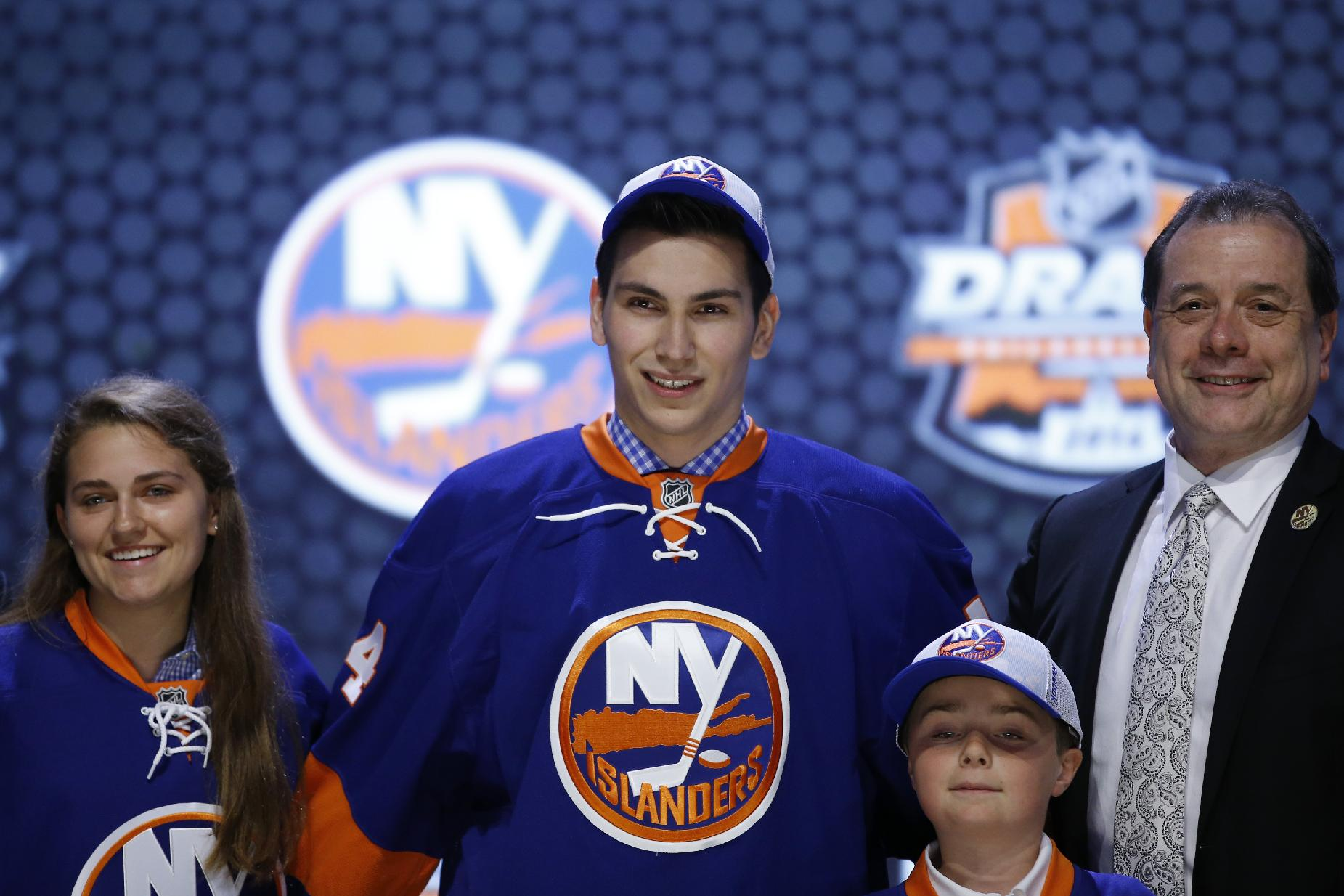Michael Dal Colle stands with New York Islanders officials after being chosen fifth overall during the first round of the NHL hockey draft, Friday, June 27, 2014, in Philadelphia