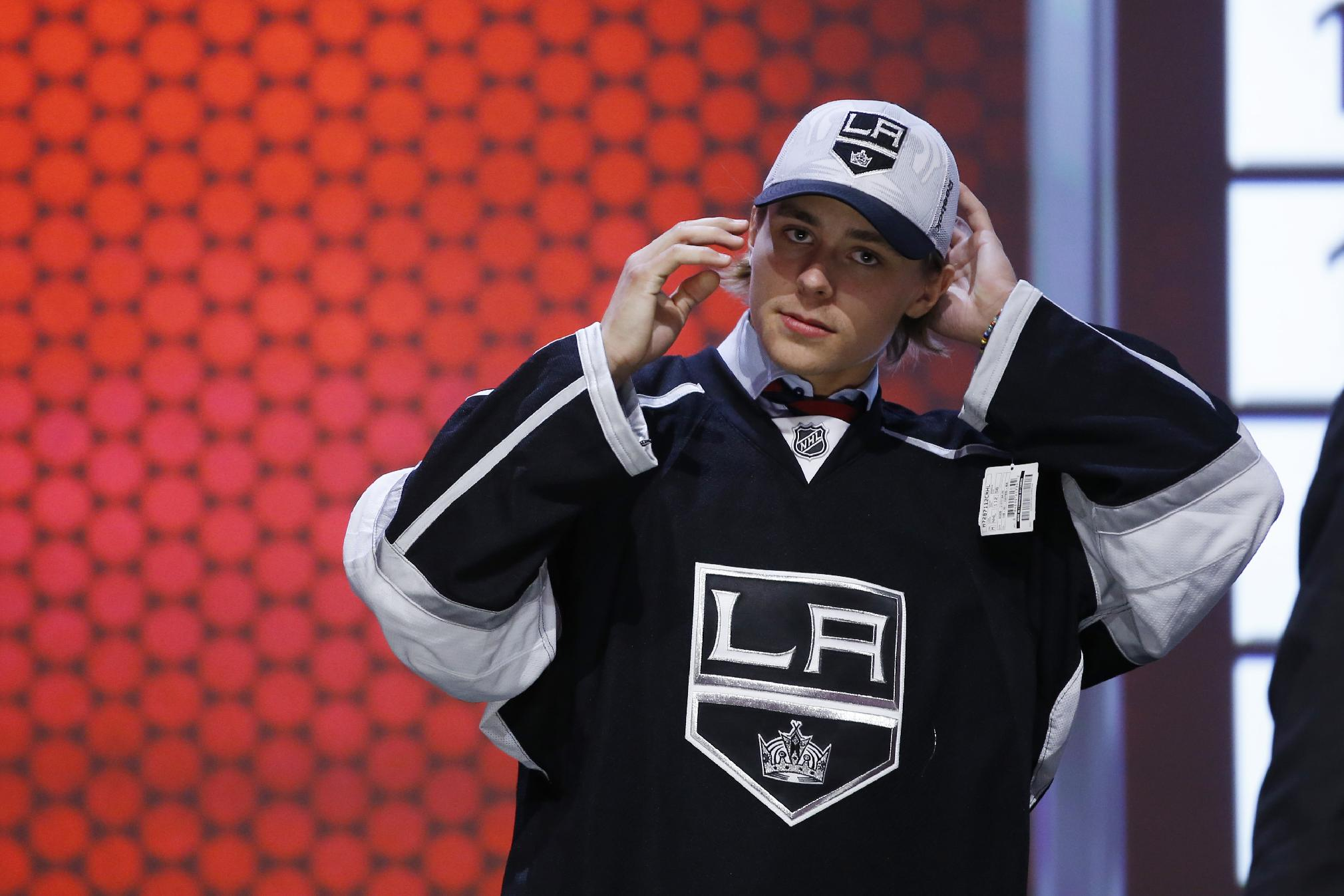 Adrian Kempe walks off the stage after being chosen 29th overall by the Los Angeles Kings during the first round of the NHL hockey draft, Friday, June 27, 2014, in Philadelphia