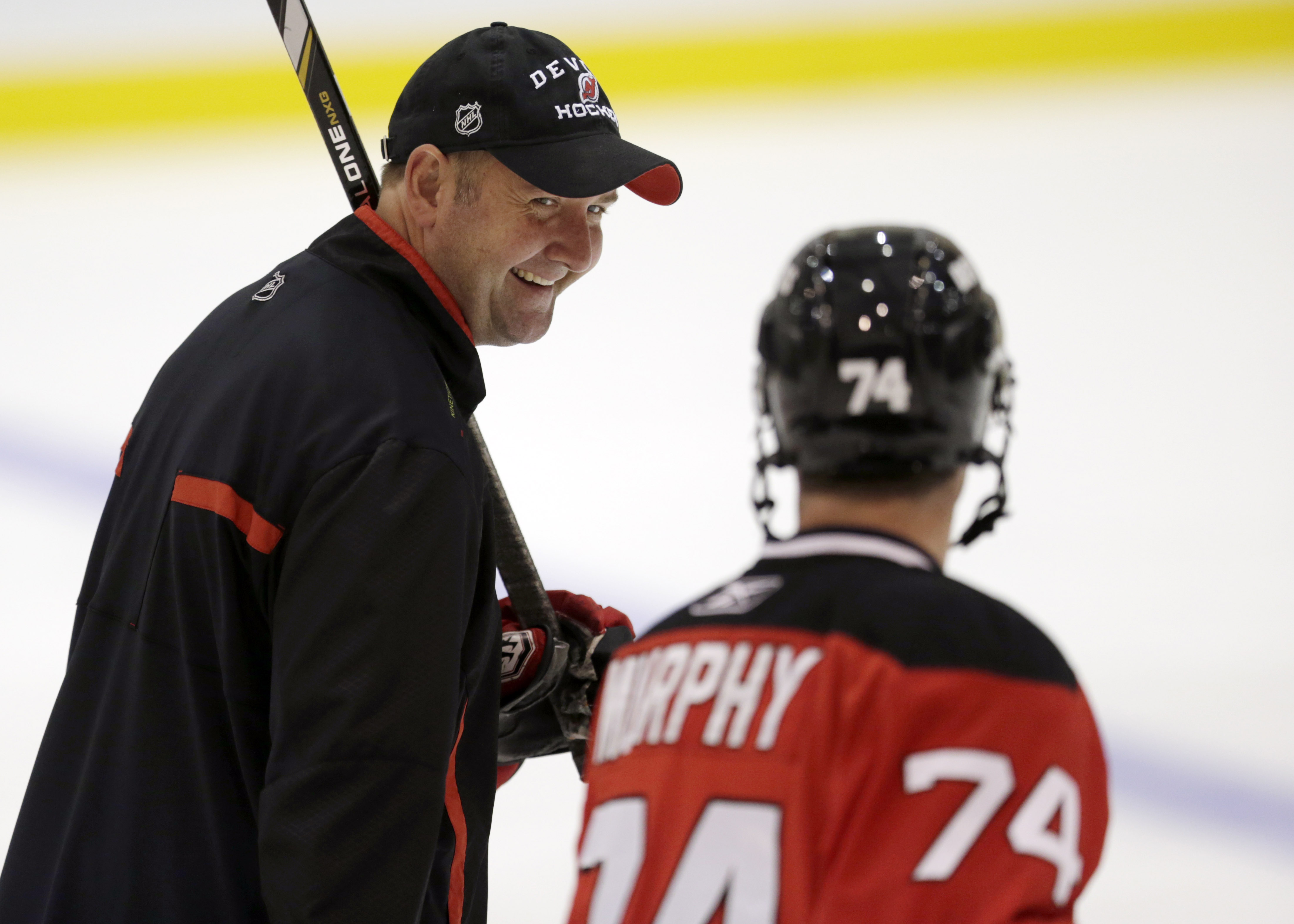 New Jersey Devils head coach Peter DeBoer, left, talks to Darcy Murphy during the team's NHL hockey rookies camp, Tuesday, July 15, 2014, in Newark, N.J