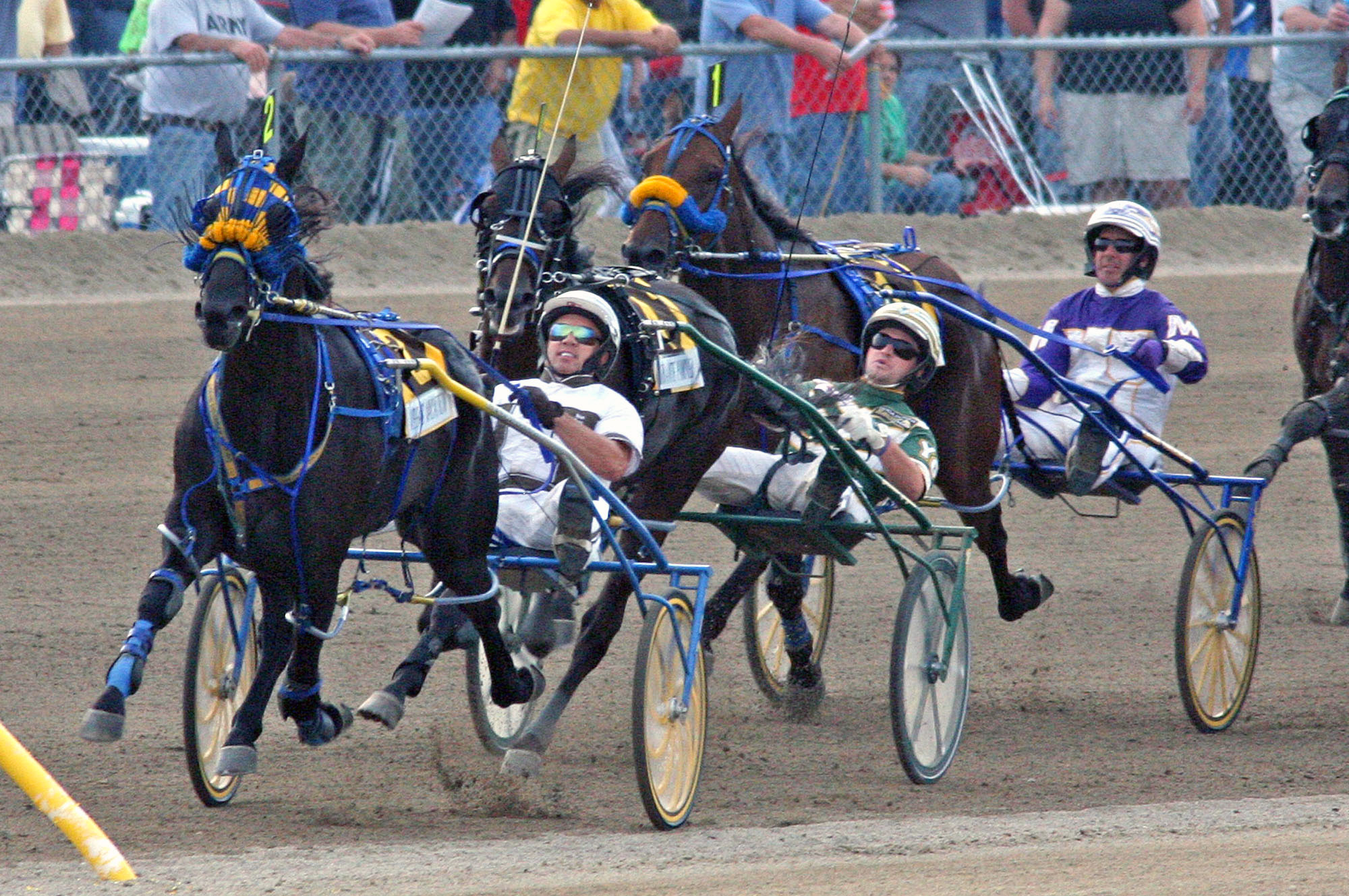 Driver Brian Sears, driving Vegas Vacation (2), leads the turn into the stretch ahead of Urbanite Hanover(4), driven by Yannick Gingras, and Lucan Hanover(1), driven by David Miller, to win the Little Brown Jug harness race for three-year-old pacers at the Delaware County Fairgrounds in Delaware, Ohio, Thursday, Sept. 19, 2013. Urbanite Hanover finished second and Lucan Hanover finished third