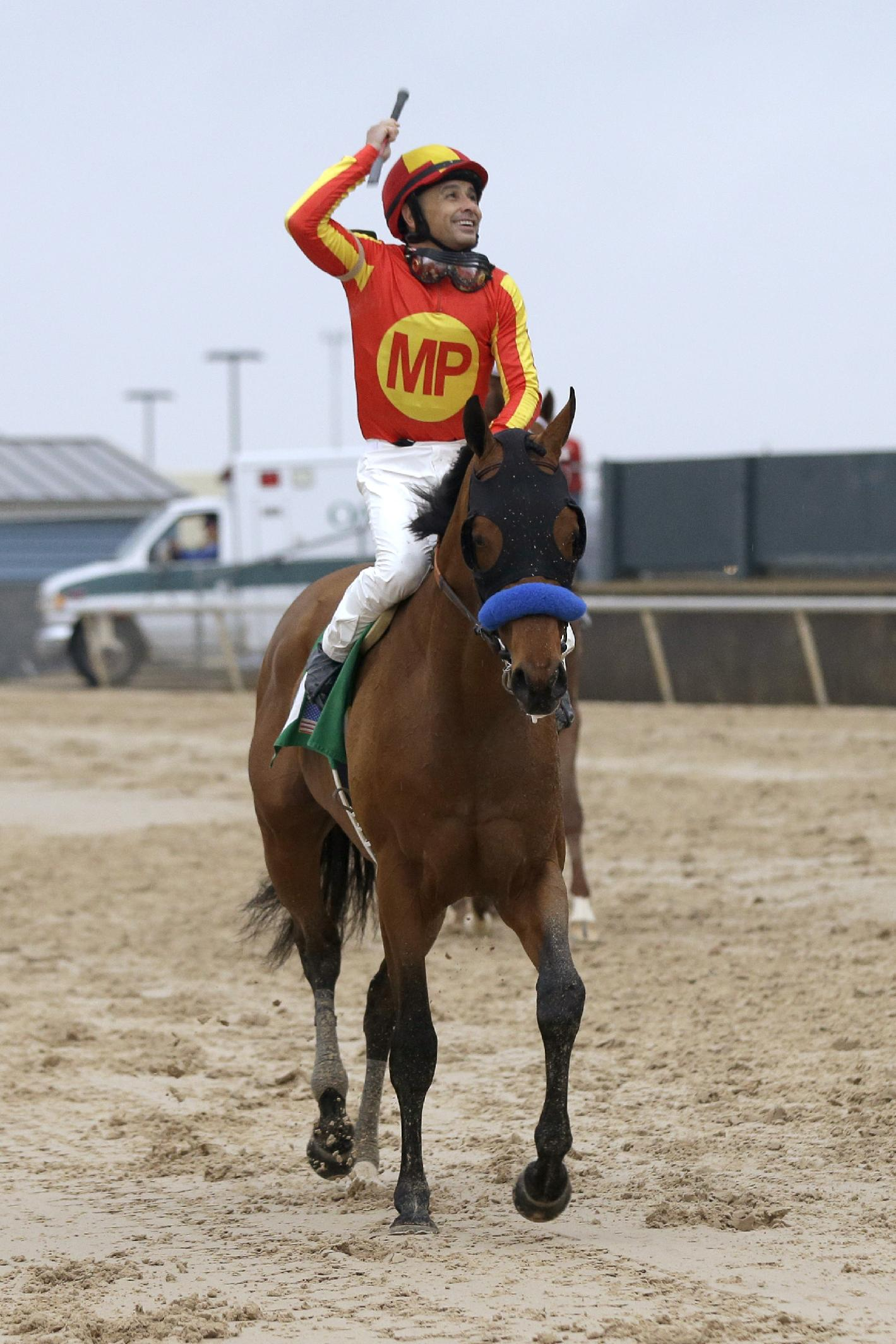 Jockey Mike Smith raises his whip as he rides Hoppertunity back towards the grandstand after winning the $600,000 Rebel Stakes horse race at Oaklawn Park in Hot Springs, Ark., Saturday, March 15, 2014