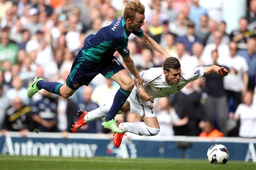 Tottenham Hotspur's Gareth Bale, right, goes down to the ground with Sunderland's Sebastian Larsson and earns a yellow card for diving during the English Premier League soccer match at White Hart Lane, London, Sunday May 19, 2013