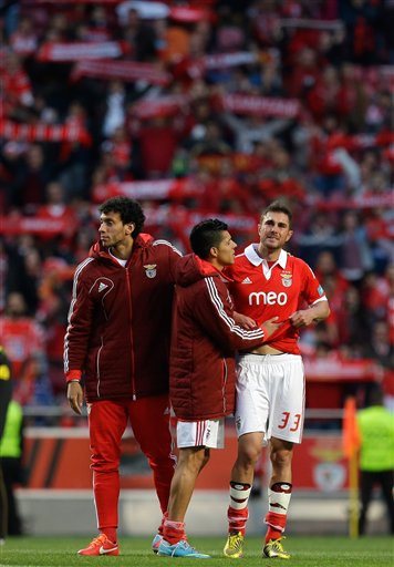 Jardel Vieira, from Brazil, right, is comforted by teammate Enzo Perez, from Argentina, and Roderick, left, at the end of their Portuguese league last round soccer match with Moreirense Sunday, May 19 2013, at Benfica's Luz stadium in Lisbon. Benfica won the match 3-1 but lost the championship to FC Porto by one point