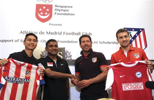 Singapore's soccer team captain Shahril Ishak, left, and coach V. Sudramoorthy, second from left, pose with Atletico Madrid coach Diego Simeone, third from left, and captain Gabriel Fernandez in Singapore on Monday, May 20, 2013. The Spanish soccer team is here to play a charity match against Singapore's soccer team to promote the sport to young soccer players