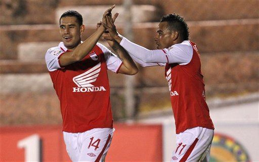 Wilder Medina of Colombia's Independiente Santa Fe, right, celebrates with his teammate John Valencia after scoring against Peru's Real Garcilaso during a Copa Libertadores quarterfinal soccer match in Cuzco, Peru, Wednesday, May 22, 2013