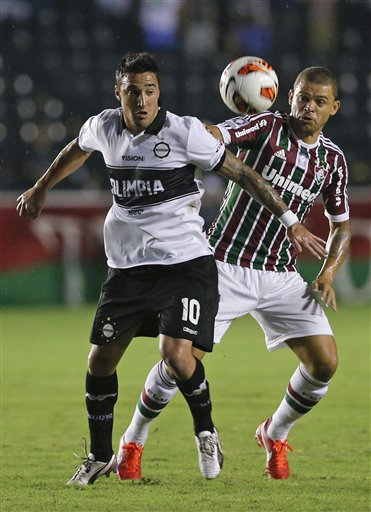 Paraguay's Olimpia Juan Manuel Salgueiro, left, vies for the ball against Brazil's Fluminense Edinho, right, during a Copa Libertadores soccer match in Rio de Janeiro, Brazil,  Wednesday, May 22, 2013