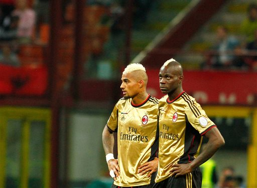In this Sunday May 12, 2013, file photo, AC Milan players Kevin Prince Boateng, left, and Mario Balotelli look toward the stands during a stoppage in play in a Serie A soccer match between AC Milan and AS Roma, at Milan's San Siro Stadium.  The game was stopped for almost two minutes because of racial abuse by Roma fans towards Balotelli and Boateng