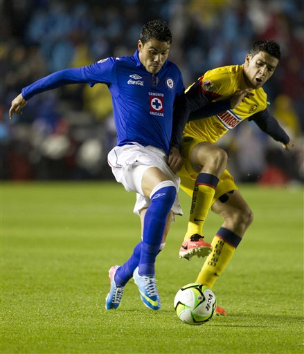 Cruz Azul's Pablo Barrera, left, fights for the ball with America's Raul Jimenez during the Mexico league first leg soccer final match in Mexico City, Thursday, May 23, 2013