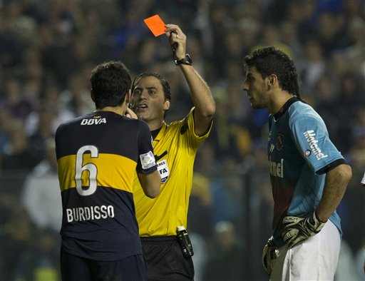 Referee Mauro Vigliano shows the red card to Argentina's Boca Juniors' Guillermo Burdisso, left, as Argentina's Newell's Old Boys' goalkeeper Nahuel Guzman look on during a Copa Libertadores quarterfinal soccer match in Buenos Aires, Argentina, Friday, May 24, 2013. The match ended in a 0-0 draw