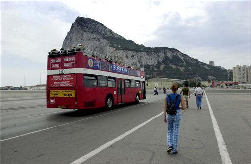 In this Aug. 26, 2001 file photo, tourists walk and take a bus from the Spanish border into Gibraltar. Gibraltar has been accepted as a full member by the UEFA Congress, becoming Europe's 54th official football nation it was announced Friday May 24, 2013. The move had previously been resisted by some politicians in neighbouring Spain, who wanted to stop the the tiny British territory on the southern tip of Spain from joining UEFA. The decision will allow Gibraltar to enter into the qualifying competition for the 2016 European Championship