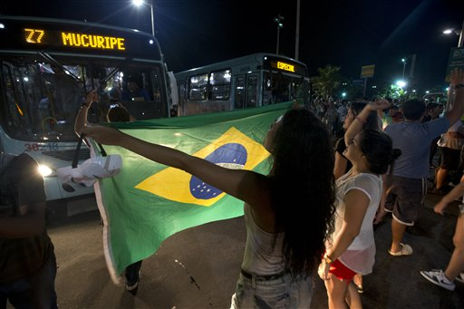 A demonstrator, holding a Brazilian flag, blocks a street during a small protest in Fortaleza. (AP)