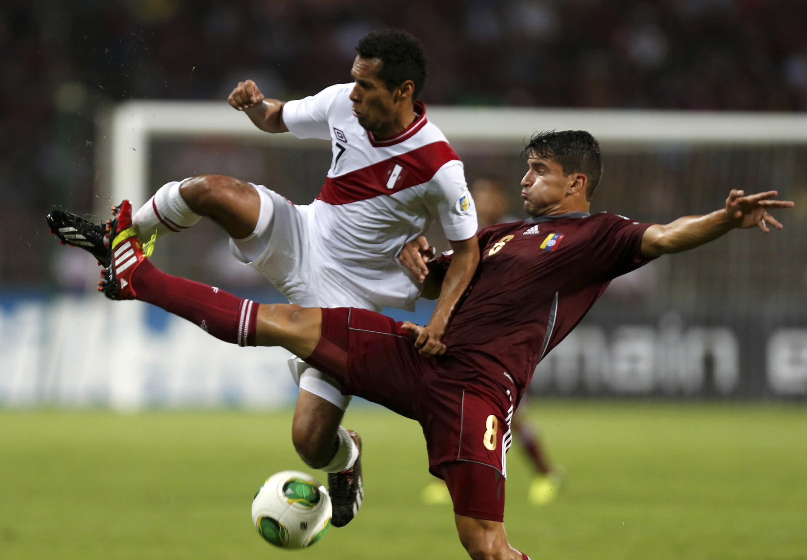 Peru's Carlos Lobaton, left, fights for the ball with Venezuela's Tomas Rincon during a World Cup 2014 qualifying soccer match in Puerto La Cruz, Venezuela, Tuesday, Sept. 10, 2013