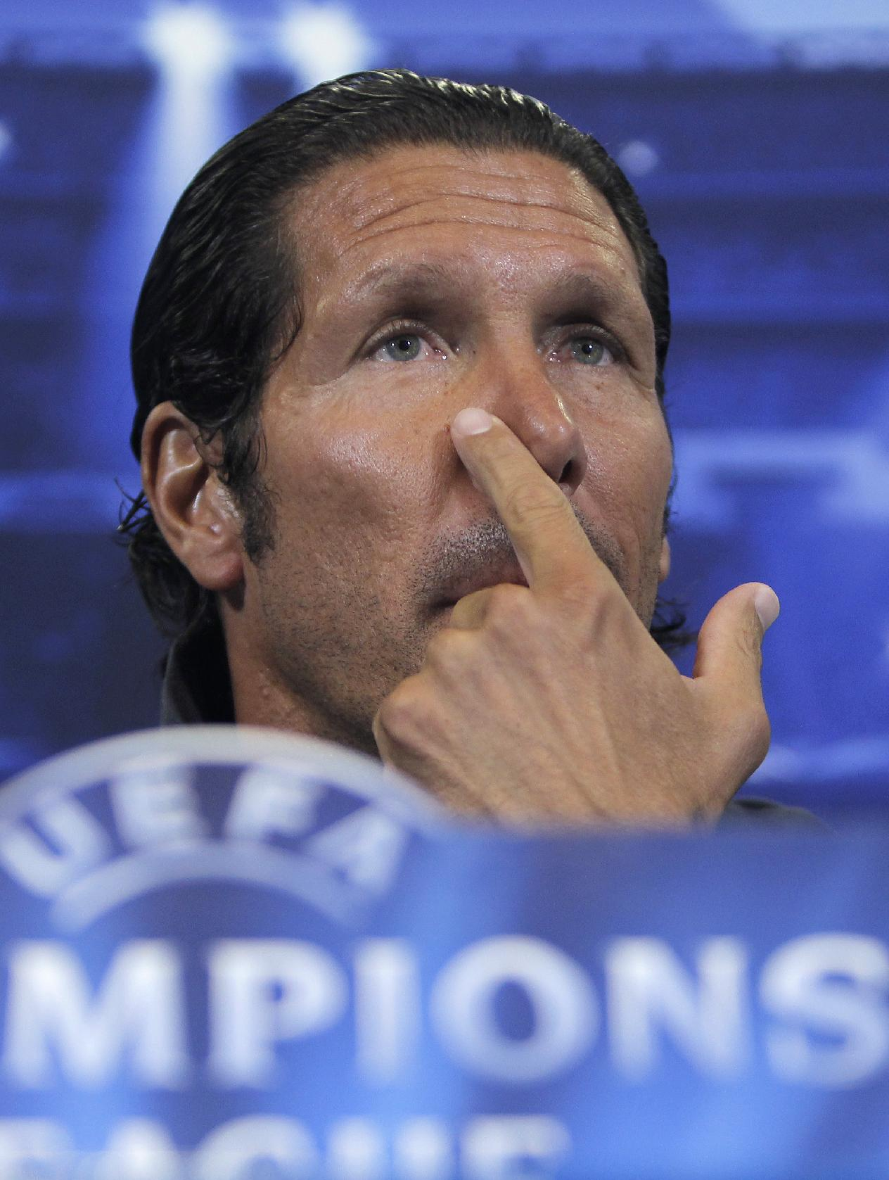Atletico de Madrid's coach Diego Simeone puts his hand to his face during a press conference prior the Champions League Group G soccer match between Atletico de Madrid and Zenit in Madrid, Spain, Tuesday, Sept. 17, 2013. Atletico play Zenit in Wednesday