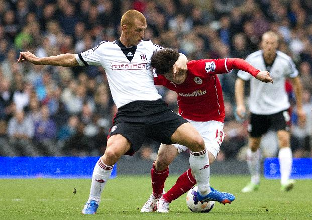 Fulham's Steve Sidwell, left, fights for the ball with Cardiff City's Kim Bo-Kyung during their English Premier League soccer match at the Craven Cottage stadium, in London, Saturday, Sept. 28, 2013