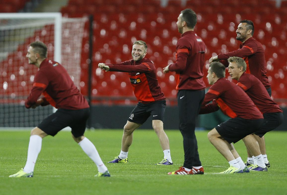 Poland's soccer team captain Jakub Blaszczykowski, second left, smiles as he stretches during a training session at Wembley Stadium in London, Monday, Oct. 14, 2013. England will play Poland in a World Cup Group H qualification match at Wembley stadium in London on Tuesday