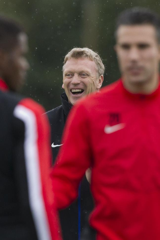 Manchester United's manager David Moyes, centre, smiles during a training session at Carrington training ground in Manchester, Tuesday, Oct. 22, 2013. Manchester United will play Real Sociedad in a Champion's League Group A soccer match on Wednesday