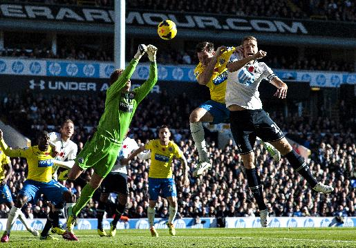 Tottenham Hotspur's Michael Dawson, right, jumps for the ball with Newcastle United's Michael Williamson and Tim Krul, left, during their English Premier League soccer match at the White Hart Lane stadium in London, Sunday Nov. 10, 2013