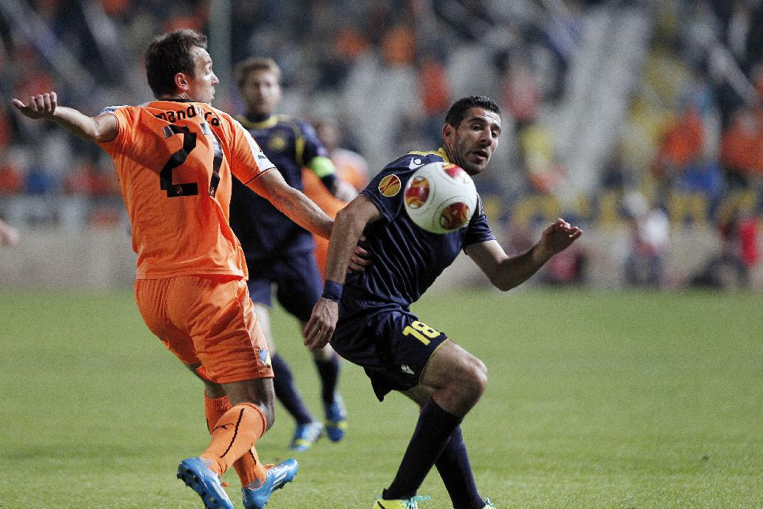 APOEL FC'S Gustavo Manduca , left, fights for the ball with Eytan Tibi of Maccabi Tel-Aviv during their Europa League group F soccer match at GSP stadium in Nicosia, Cyprus, Thursday, Nov. 28, 2013