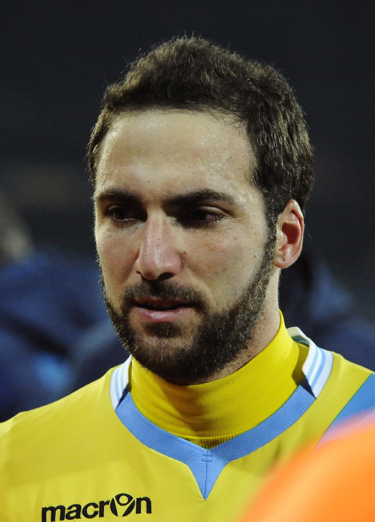Napoli's Gonazalo Higuain walks off the field at the end of a Champions League, group F, soccer match between Napoli and Arsenal, at the Naples San Paolo stadium, Italy, Wednesday, Dec. 11, 2013. Ten-man Arsenal advanced to the Champions League knockout phase for the 14th consecutive year despite a 2-0 loss Wednesday at Napoli, which was eliminated. Gonzalo Higuain scored in the 73rd minute but the San Paolo stadium was soon silenced when word arrived that Borussia Dortmund had scored a late goal in a 2-1 win at Marseille to win Group F