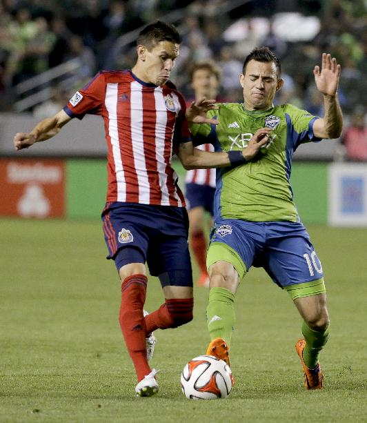 Chivas USA midfielder Eric Avila, left, battles Seattle Sounders FC midfielder Marco Pappa for the ball during second half a MLS soccer match Saturday, April 19, 2014 in Carson, Calif