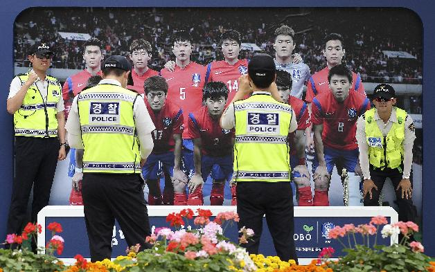 Police officers take their souvenir photos in front of a picture showing South Korean national soccer team players in Seoul, South Korea, Monday, June 16, 2014. South Korea will face Russia, Belgium and Algeria in the 2014 Brazil World Cup soccer tournament