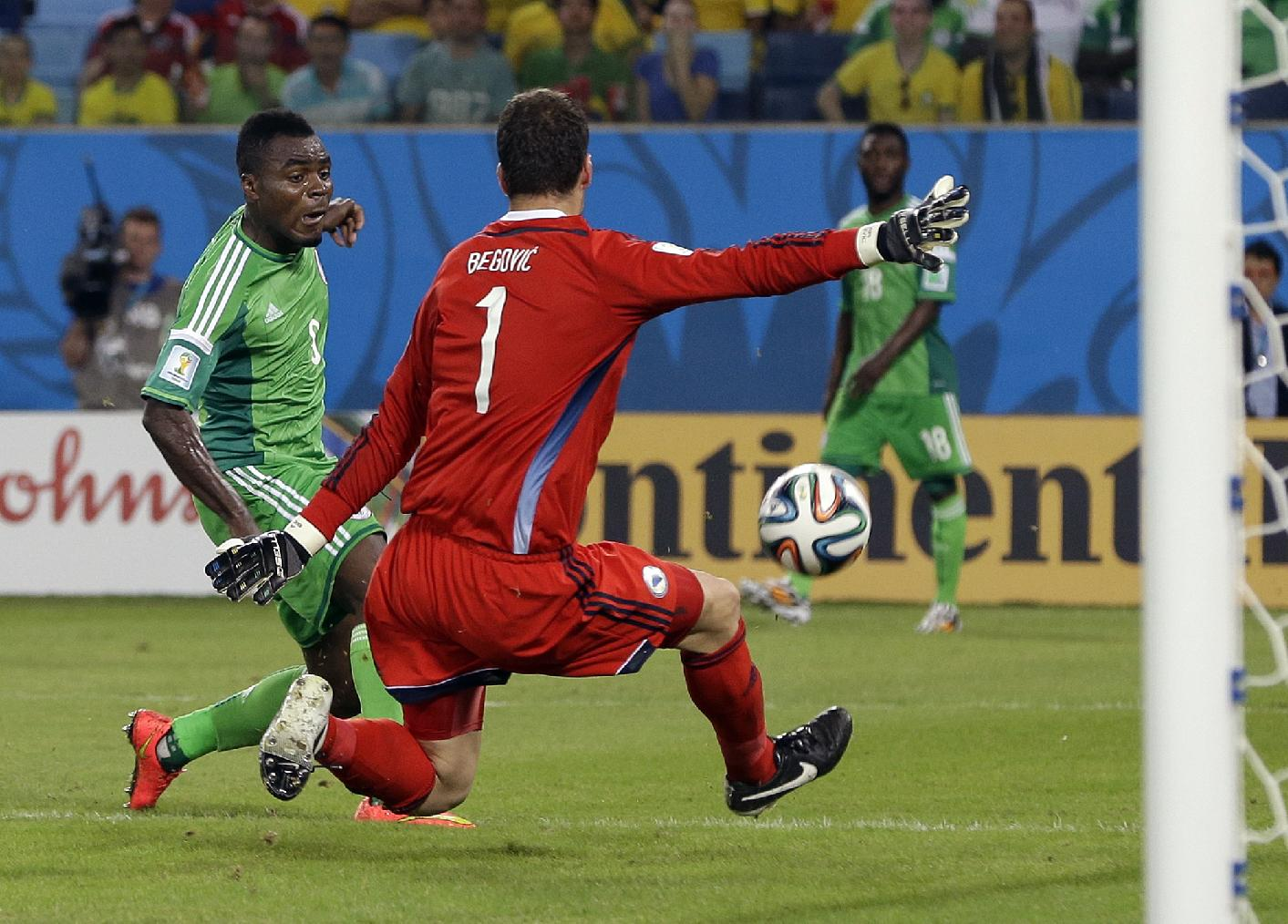 Nigeria's Emmanuel Emenike, left, shoots against Bosnia's goalkeeper Asmir Begovic, but the ball goes wide during the group F World Cup soccer match between Nigeria and Bosnia at the Arena Pantanal in Cuiaba, Brazil, Saturday, June 21, 2014