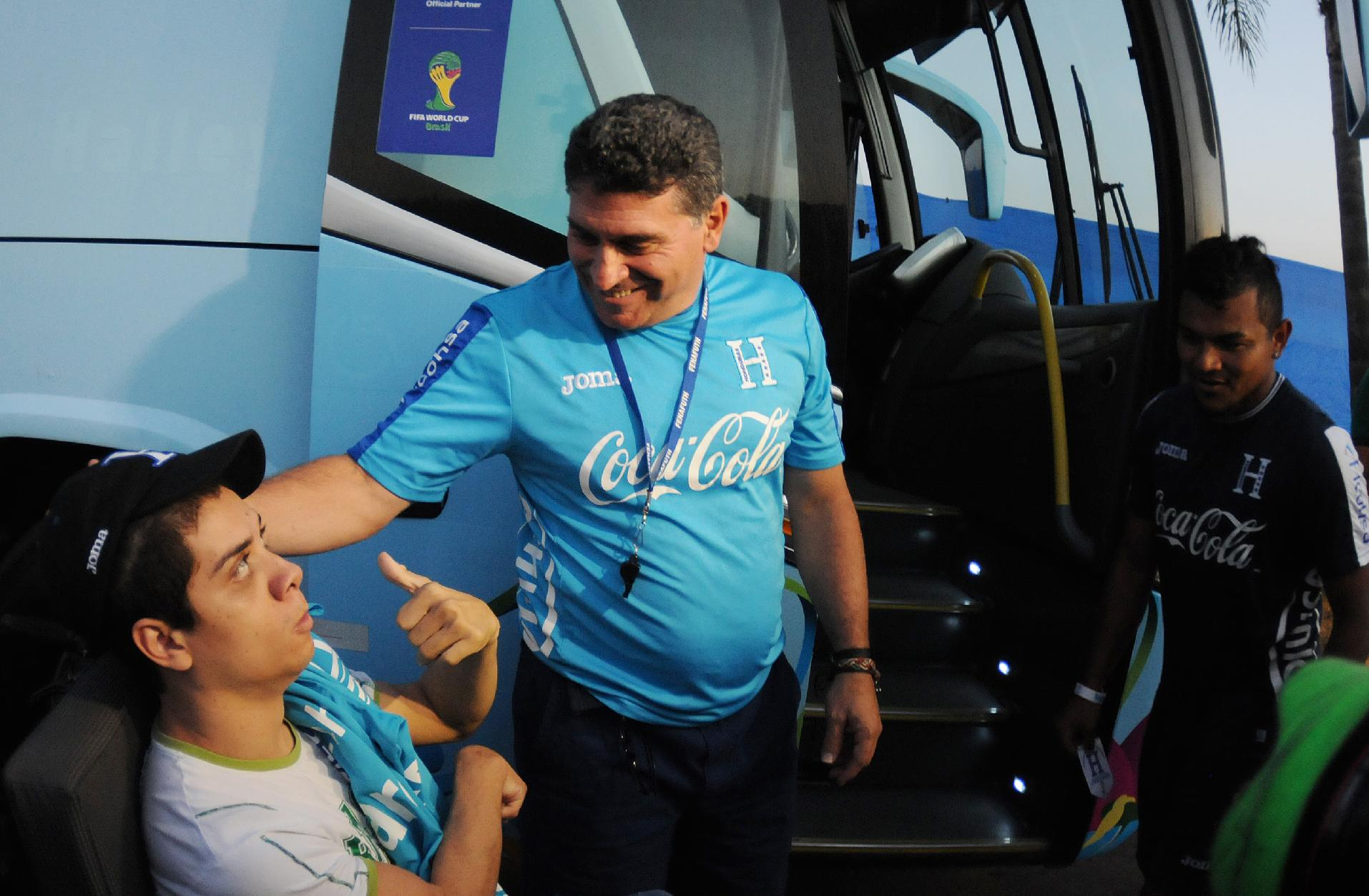 Honduras'  head coach Luis Fernando Suarez greets a child with disabilities before a training session of the Honduran national soccer team, in Porto Feliz, Brazil, Sunday, June 22, 2014. Languishing in bottom spot in Group E after two defeats, Honduras has only a very slim chance of qualifying for the knockout stages of the World Cup