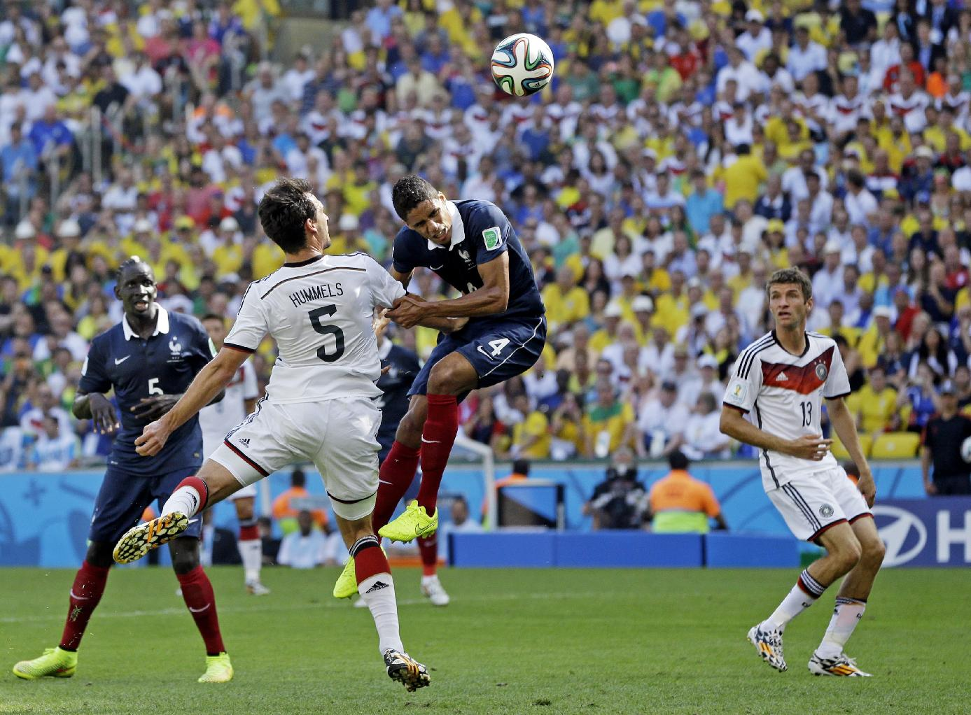 Germany's Mats Hummels heads the ball past France's Raphael Varane to score his side's first goal during the World Cup quarterfinal soccer match at the Maracana Stadium in Rio de Janeiro, Brazil, Friday, July 4, 2014