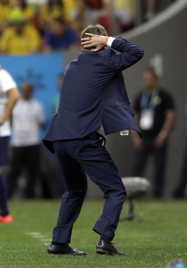 Netherlands' head coach Louis van Gaal demonstrates to officials where one of his players was hit during the World Cup third-place soccer match between Brazil and the Netherlands at the Estadio Nacional in Brasilia, Brazil, Saturday, July 12, 2014