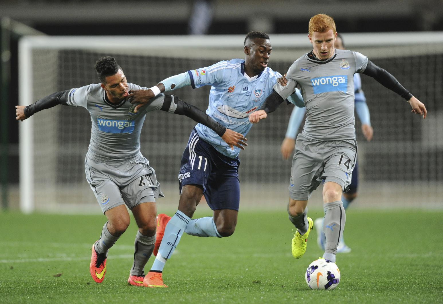 Newcastle United's Jack Colback, right, controls the ball as Emmanuel Riviere holds back Sydney FC's Bernie Ibini-Isei, center, during the first match of the Football United Tour at Forsyth Barr Stadium, Dunedin, New Zealand, Tuesday, July 22, 2014