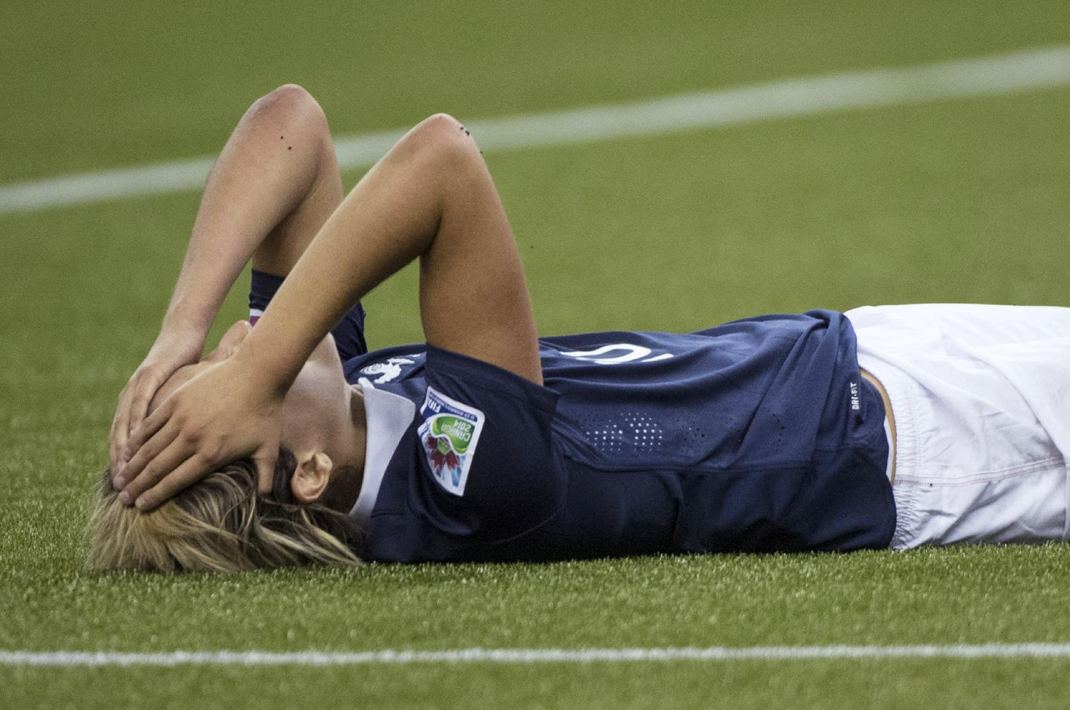 France's Claire Lavogez lies on the pitch after missing a scoring opportunity against Germany during extra time in the second half of a FIFA U-20 women's World Cup semifinal in Montreal on Wednesday, Aug. 20, 2014. Germany won 2-1